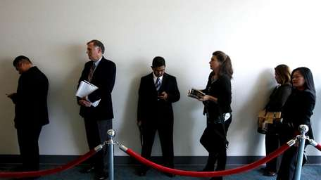 Job searchers wait in line during a career