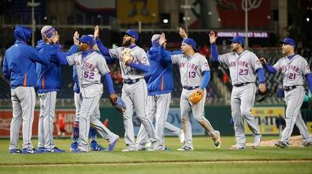 The Mets celebrate on the field after the