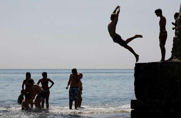 Swimmers jump into the sea from a pier
