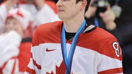 Canada's Sidney Crosby stands with his gold medal