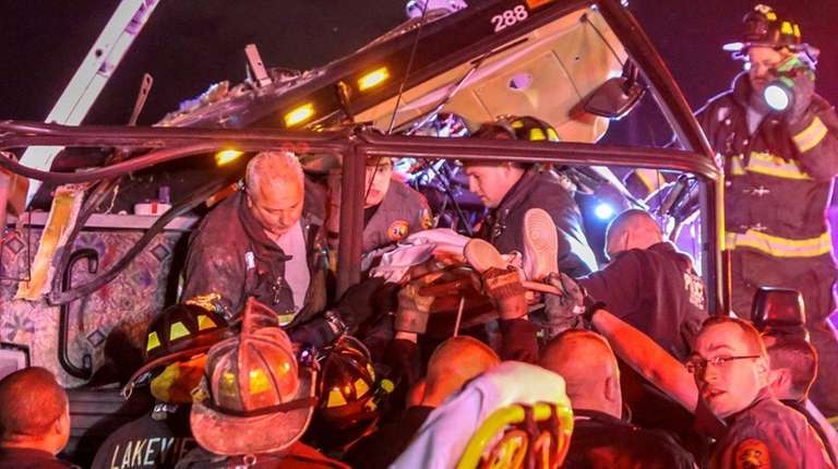 Firefighters and police officers extricate an injured student
