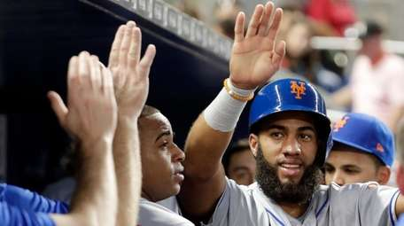 Mets' Amed Rosario is congratulated in the dugout