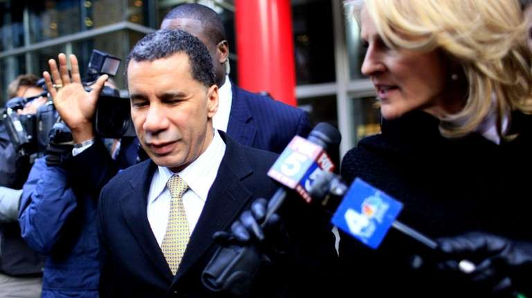 Gov. David Paterson, left, leaves his midtown office,
