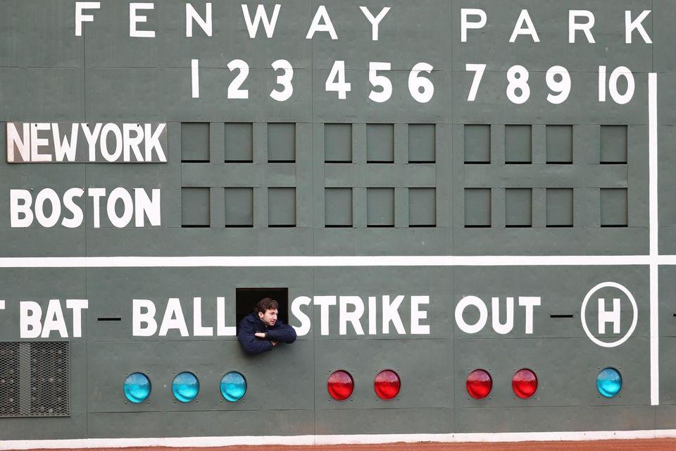 A scorekeeper looks on from inside the Green