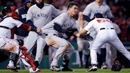 The Yankees' Tyler Austin, center, rushes Red Sox