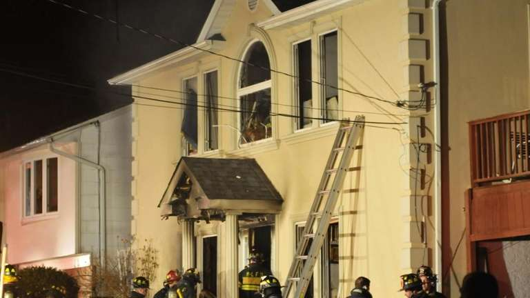 Firefighters wait for orders at the front entrance