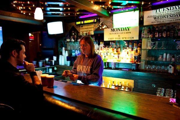 A bartender counts out change at Fins Pub