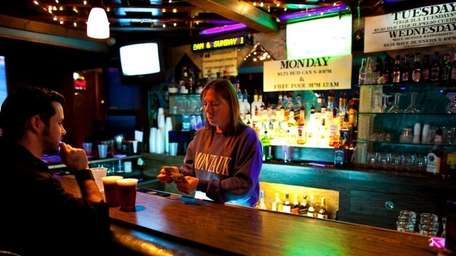 A bartender counts out change at Fins Pub