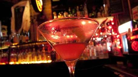 A cosmopolitan, half-drunk, sits on the bar at