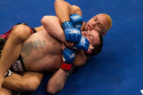 Jens Pulver, foreground, gets caught in a choke