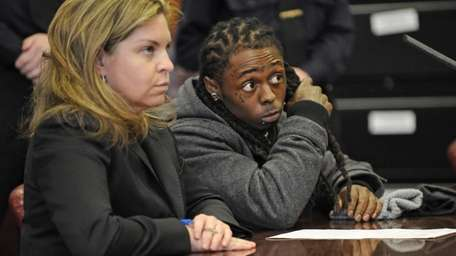 Rapper Lil Wayne listens to the judge's sentencing