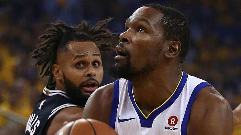 The Warriors' Kevin Durant, right, shoots against the