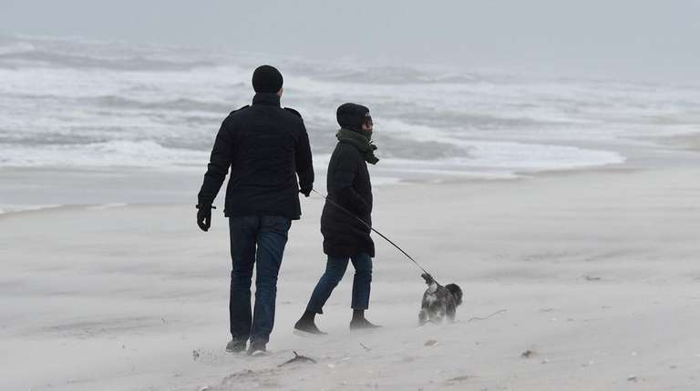 A couple walk their dog at Smith Point