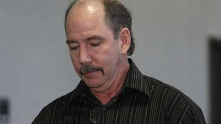 Sanitation truck driver Robert Moore leaves a Riverhead
