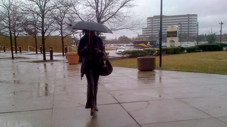 A woman walks in the rain at Nassau