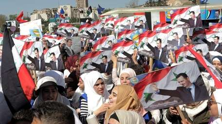 Demonstrators wave national flags and posters of Syrian