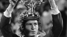 John McEnroe holds the cup after winning the