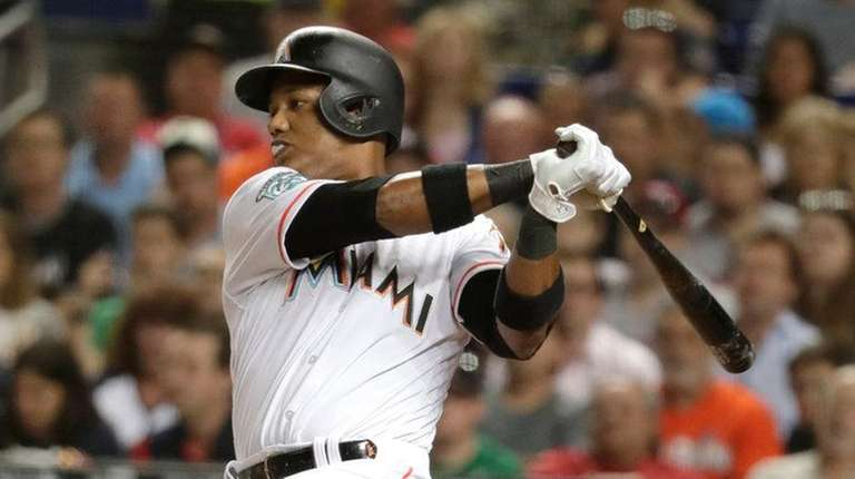 Miami Marlins' Starlin Castro, left, hits a single