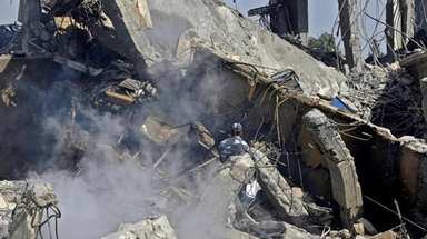 A Syrian soldier sprays water on the wreckage