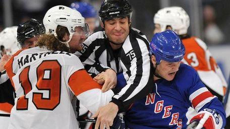 A referee gets between Philadelphia Flyers' Scott Hartnell