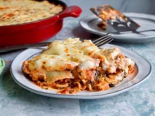 Lasagna noodles, spinach, cheeses and tomatoes make an