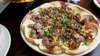 Hummus topped with chopped grilled lamb is garnished