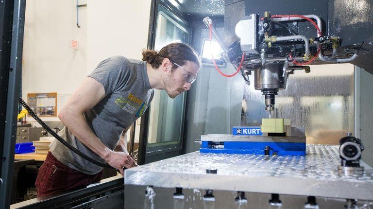 Machinist Jason Gallo operates a computer-controlled milling machine