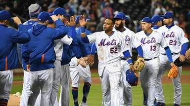 Mets players including leftfielder Yoenis Cespedes, center, celebrate