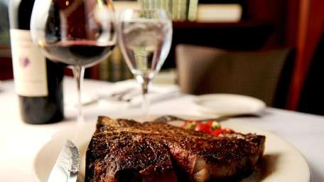 A porterhouse steak is served with a Cabernet