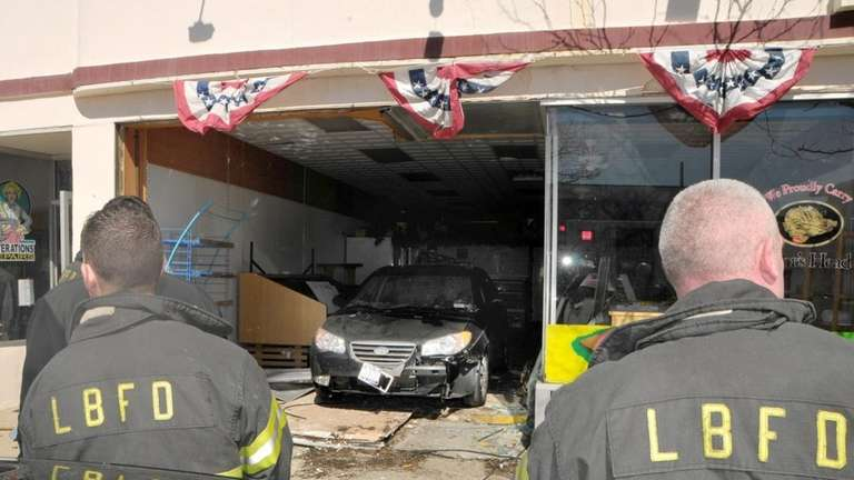 Responders inspect the scene of a store front