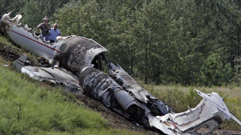 Investigators look over the debris of a Learjet