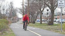 A cyclist uses the paved path built alongside