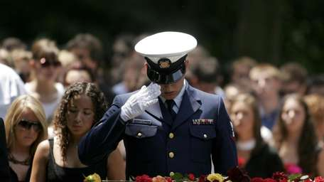 A friend salutes during the funeral service of