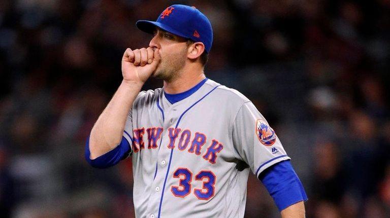 Mets starting pitcher Matt Harvey blows on his