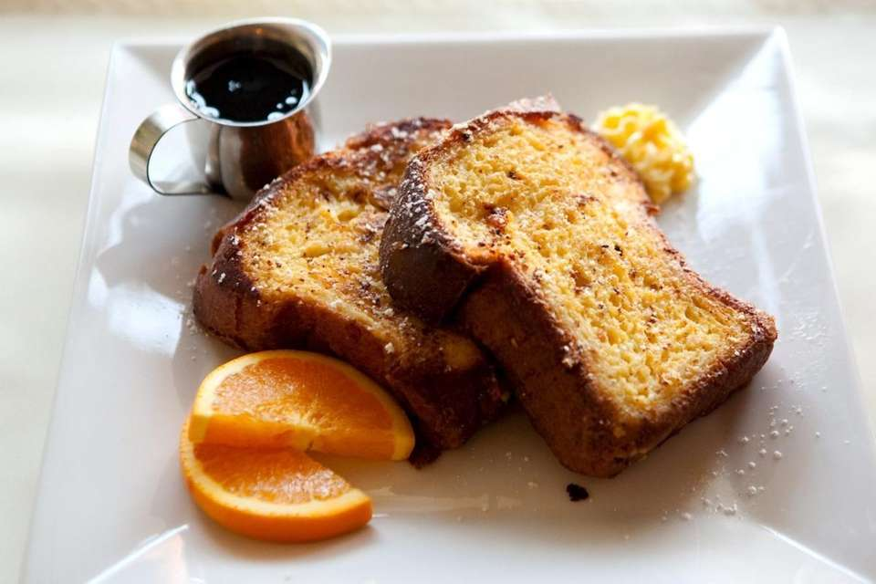 Orange french toast is served at Chat Noir