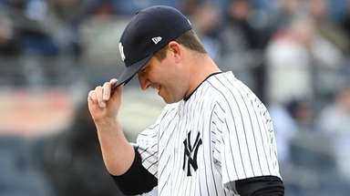 Yankees relief pitcher Adam Warren adjusts his cap