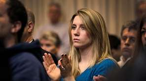 Katie Horst of Manorville applauds while listening to
