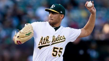 Athletics starting pitcher Sean Manaea throws to a