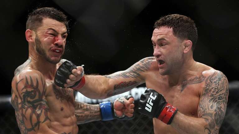 Frankie Edgar, right, hits Cub Swanson during the