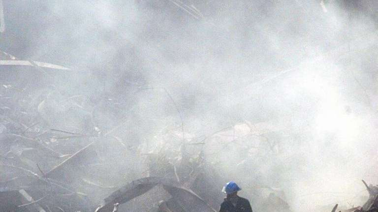 A rescue worker looks around the rubble at