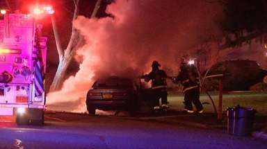 Firefighters work at the scene where a car