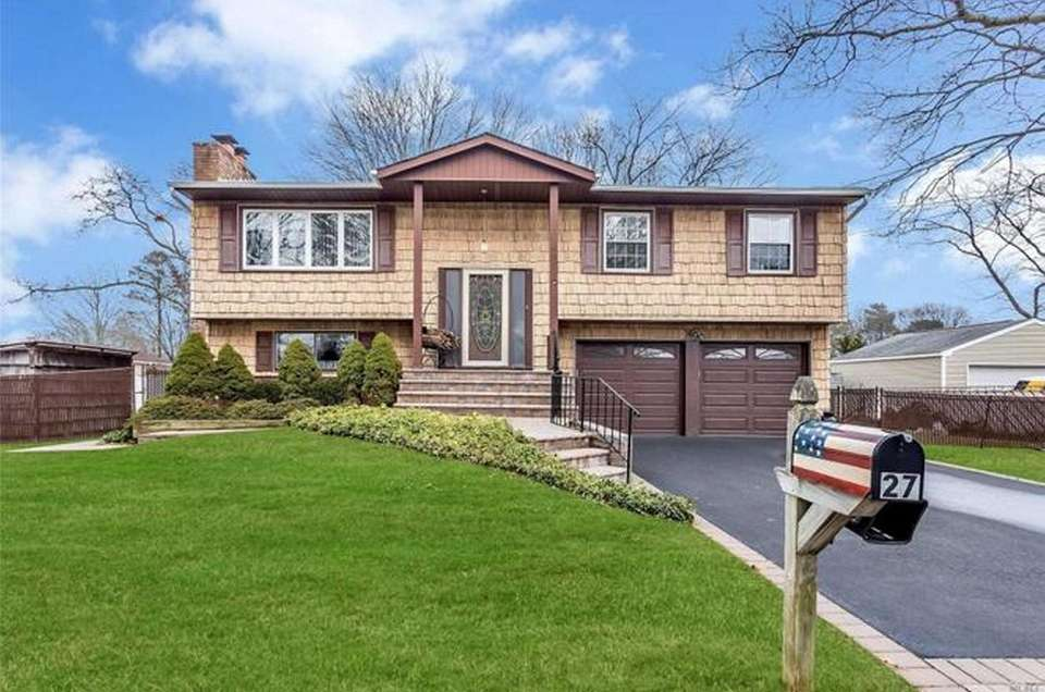 This Sayville high-ranch includes four bedrooms and two