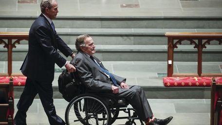Former president George W. Bush wheels his father,