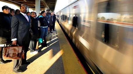Commuters wait to board an incoming westbound train