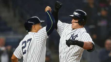 Tyler Austin, right, celebrates his three-run home run