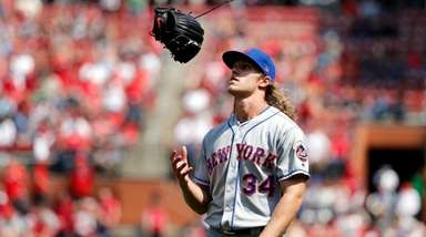 Mets starting pitcher Noah Syndergaard flips his glove