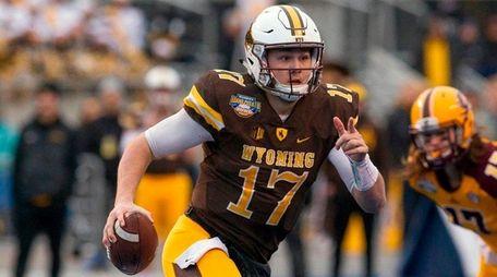 Wyoming quarterback Josh Allen runs with the ball