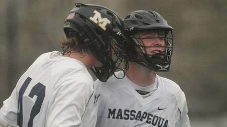 Garrett Gibbonsof Massapequa, right, gets congratulated by teammate