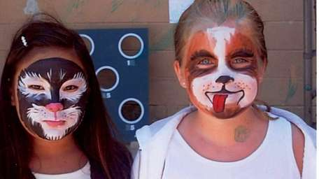 Two campers model their freshly painted faces at