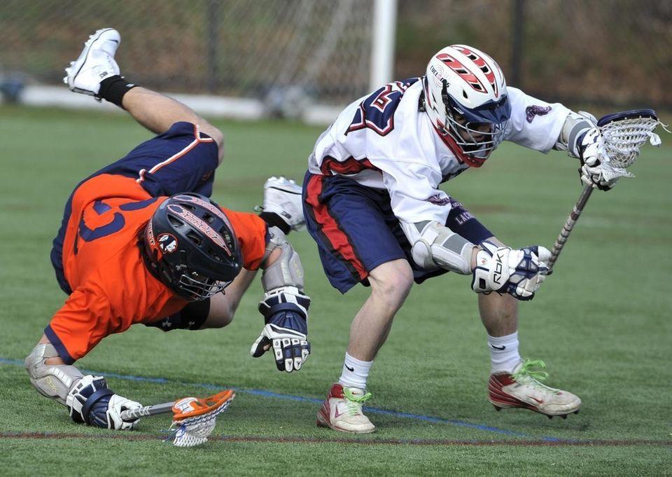 Manhasset's Drew Belinsky (32) goes airborne defending against